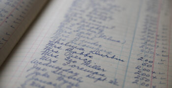 Vintage handwritten ledger of women's names and amounts with selective focus.