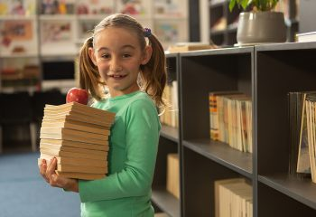 Side view of smiling Caucasian schoolgirl with books and apple standing in library at elementary school