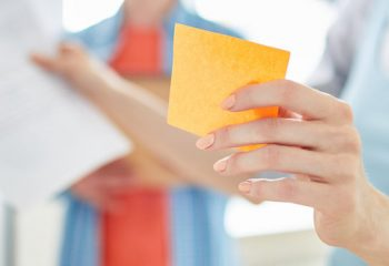 Close-up of positive manager holding adhesive note while planning project development with colleague and presenting her idea at meeting